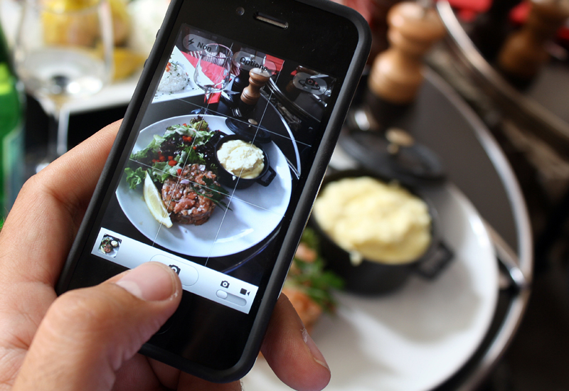 Diner taking photo of food