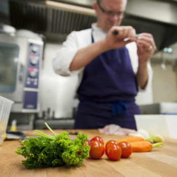 Chef in kitchen cutting vegetables